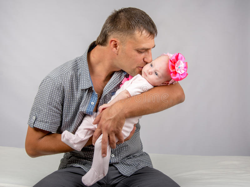 Happy dad kisses his infant daughter two months. Young dad sitting on a bed and holds her two-month baby daughter stock image
