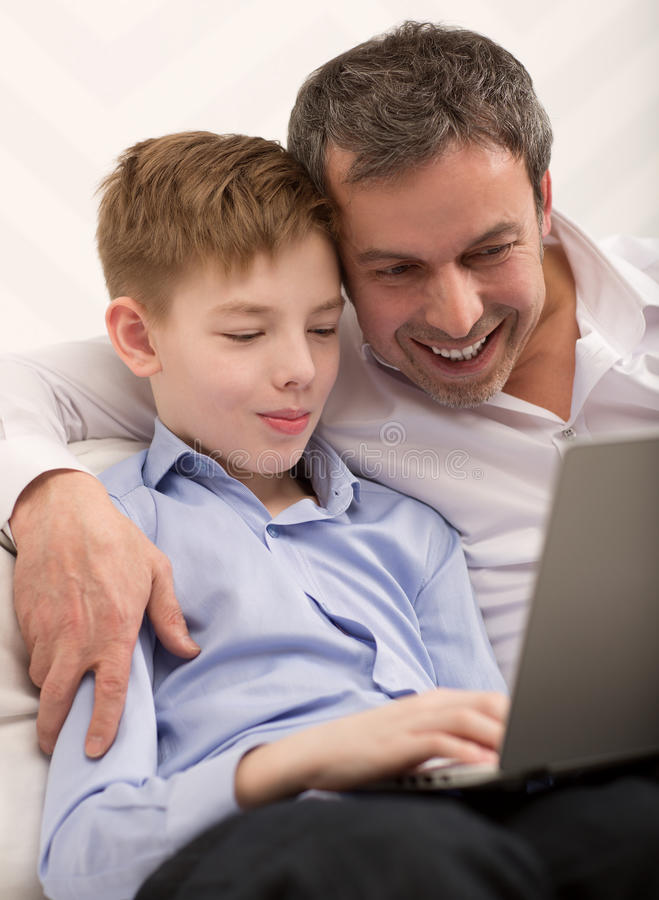 Happy dad and son with laptop at home royalty free stock photo