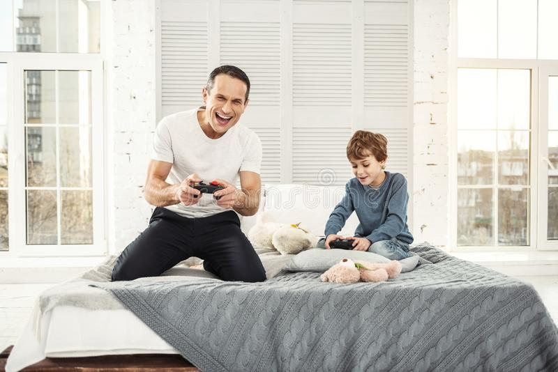 Happy dad and son playing games royalty free stock photos