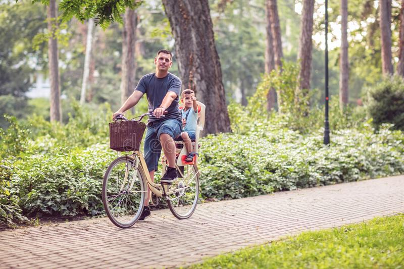 Happy Dad and son riding bicycles outdoors in a city park stock photography