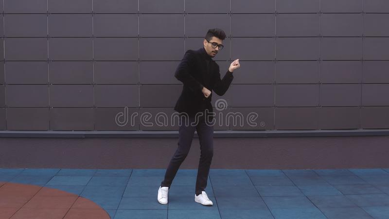 Happy dancer man wearing suit funky street dancing freestyle in the city stock photo