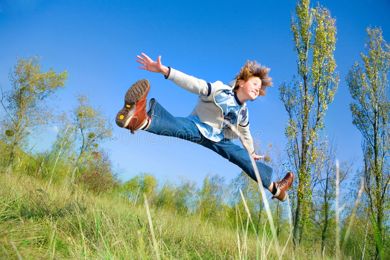 Happy dancing boy. In jeans and coat royalty free stock image