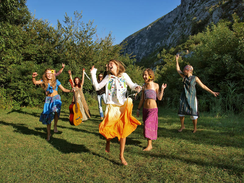 Happy dancing family. Happy big family (barefoot) band - group-best friends, looking forward to dancing, laughing, full of joy and elation on the green grass at