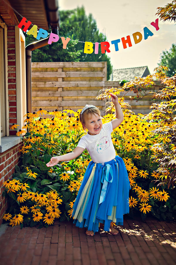 Happy dancing girl in tiara at birthday party. Portrait of little smiling girl at birthday party royalty free stock photography