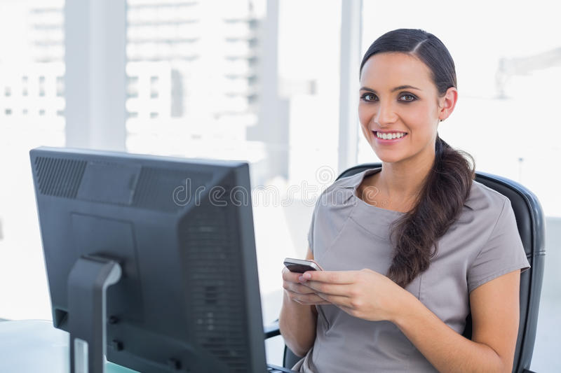 Happy dark haired businesswoman holding phone royalty free stock images