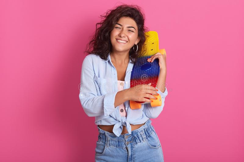Happy dark haired female enjoys extreme riding on skateboard, has curly hair, holding board in hands, looks with joyful facial. Expression, stands over rose stock photos