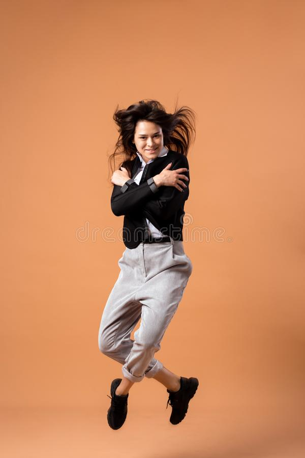 Happy dark-haired girl dressed in white shirt, gray trousers, black jacket and black sneakers jumps on the beige royalty free stock photos