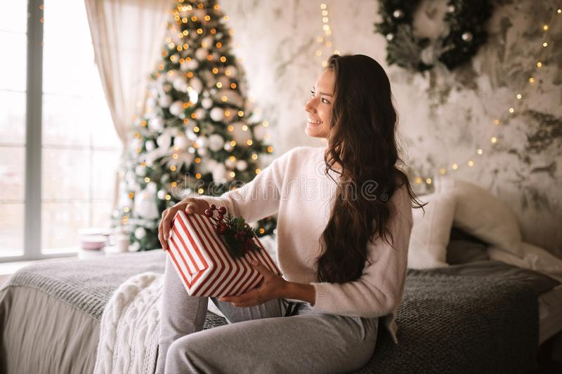Happy dark-haired girl dressed in white sweater and pants holds a New Year gift in her hands sitting on the bed with. Gray blanket and white pillows in a stock photo