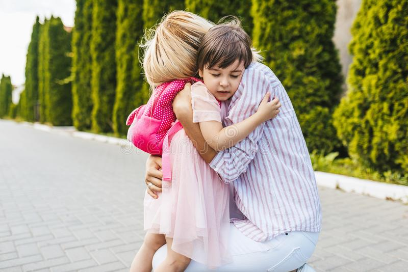 Happy daughter little girl and pretty mother embracing each other on sidewalk on the street. Mom met the child after the stock images