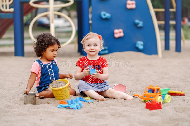Caucasian and hispanic latin babies children sitting in sandbox playing with plastic colorful toys. Happy day. Two cute Caucasian and hispanic latin babies royalty free stock photo