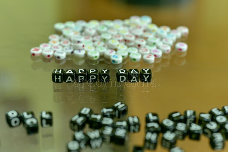 HAPPY DAY  written with Acrylic Black cube with white Alphabet Beads on the Glass Background.  stock images