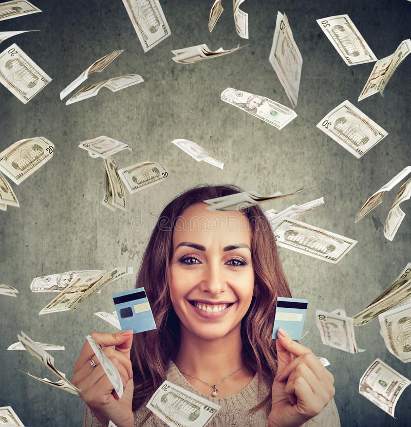 Happy debt free woman holding a credit card cut in two pieces. Under money rain stock image