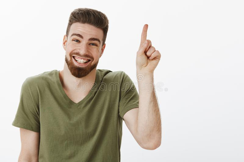 Happy delighted and carefree attractive adult man with beard laughing joyfully having great time looking delighted and royalty free stock photo