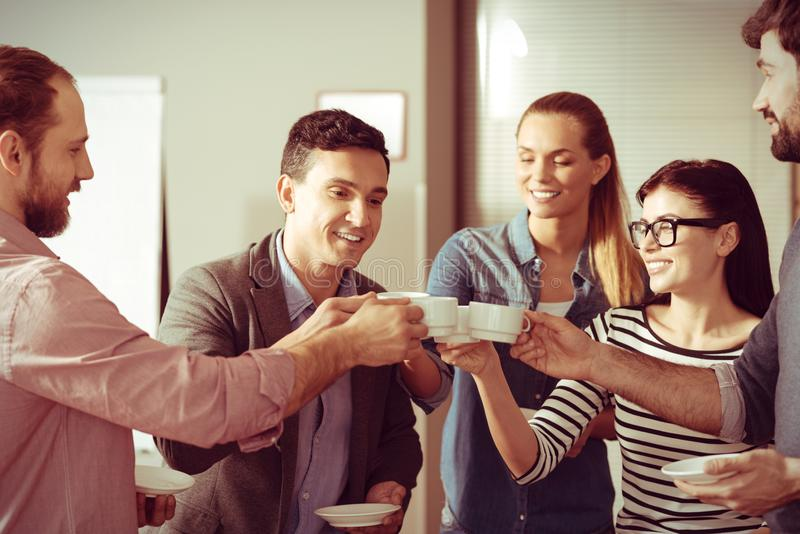 Happy delighted colleagues holding coffee cups. Cheers to us. Happy delighted young colleagues holding coffee cups and cheering with them while having a coffee royalty free stock images