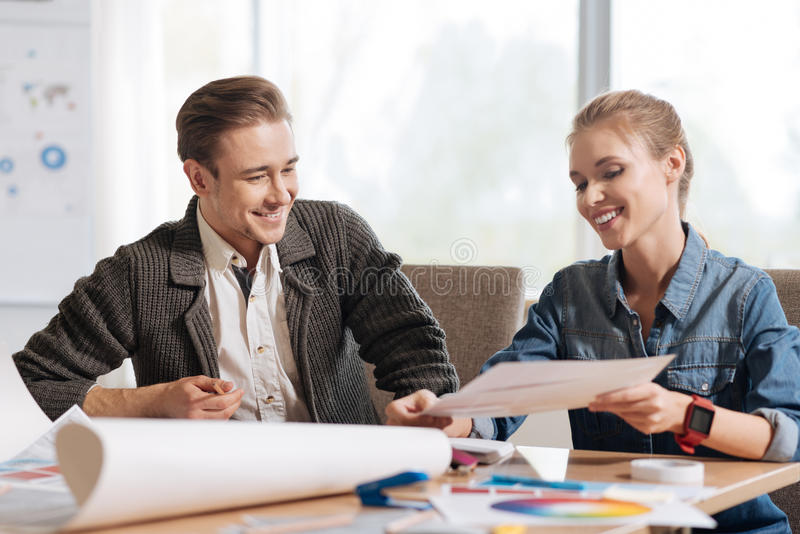 Happy delighted colleagues smiling. Positive mood. Happy delighted nice colleagues looking at the project and smiling while being in a positive mood royalty free stock photo