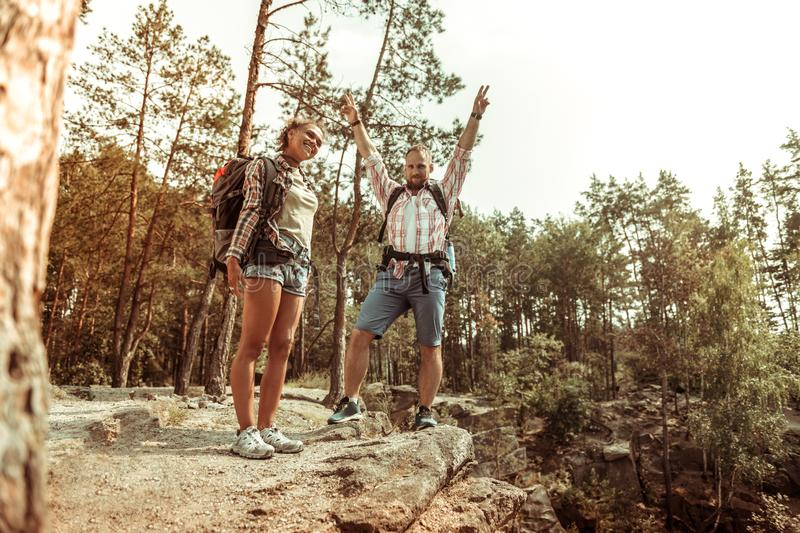 Happy delighted couple hiking in the forest royalty free stock photography