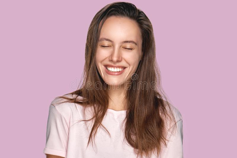 Happy delighted female with positive smile, smiles broadly, dressed in casual clothing, isolated over lavender wall royalty free stock photography