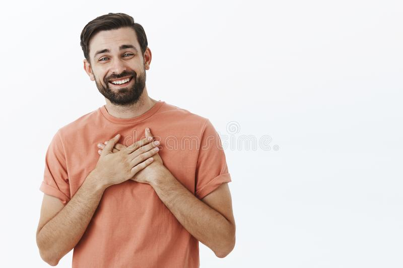 Happy delighted and grateful adult european man with beard in pink t-shirt holding palms on heart and smiling thankful royalty free stock photography
