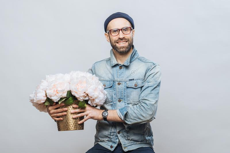 Happy delighted male buys bouquet of flowers for special occasion, wears denim jacket and denim shirt, isolated over white royalty free stock photography