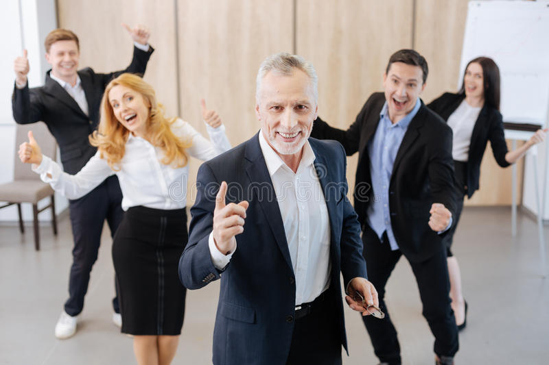 Happy delighted man standing in front of the team royalty free stock photography