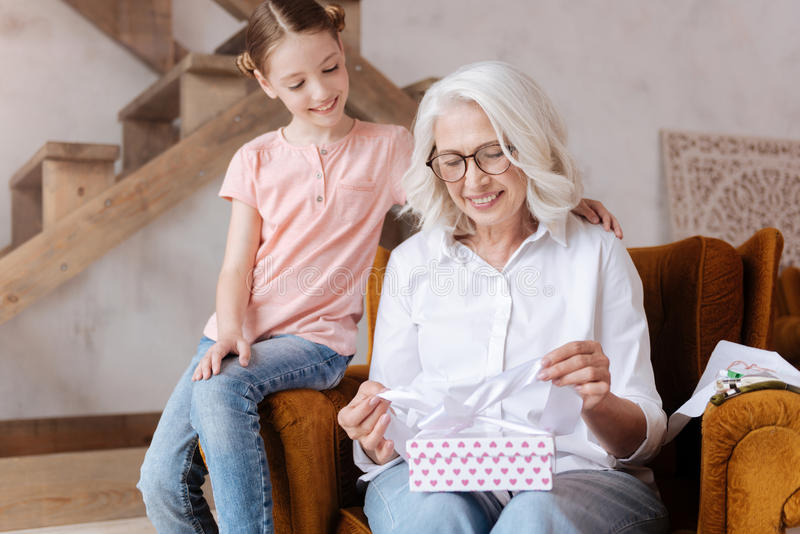 Happy delighted woman holding a gift box. Pleasant surprise. Happy delighted joyful women holding a gift box and opening it while sitting with her granddaughter stock image
