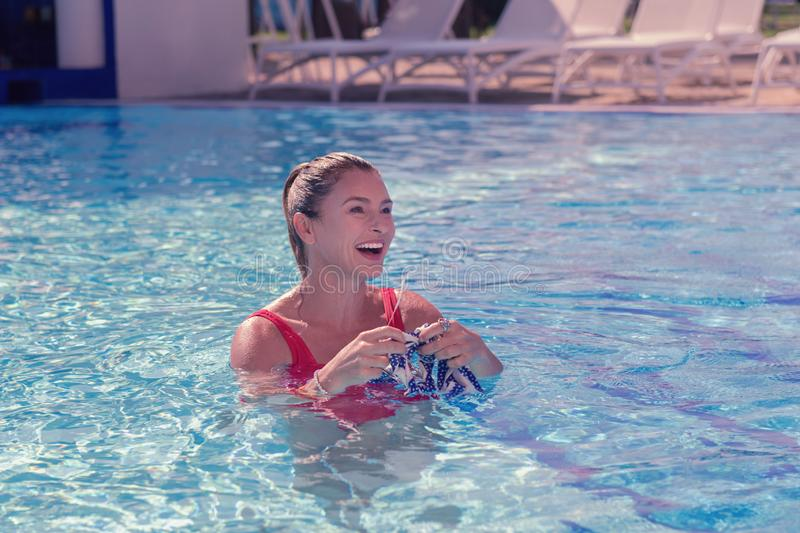 Happy delighted young woman swimming in water royalty free stock photo