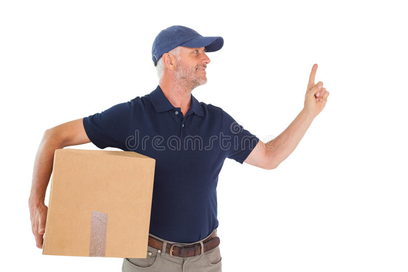Happy Delivery Man Holding Cardboard Box And Pointing Up Stock Photo