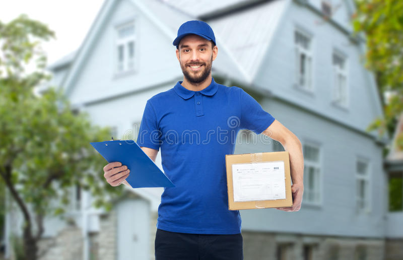 Happy delivery man with parcel box and clipboard. Home delivery service, mail, logistics, people and shipping concept - happy man with parcel box and clipboard royalty free stock image