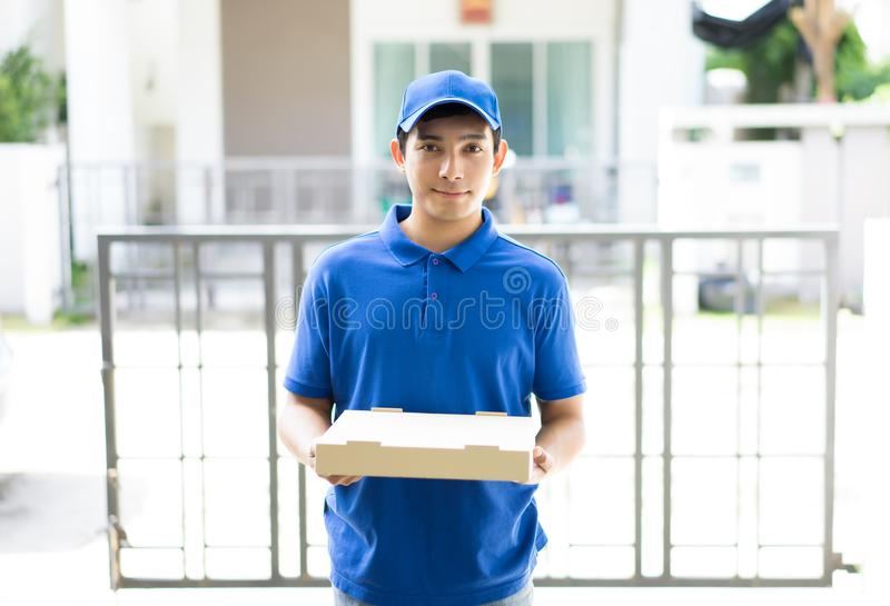Happy delivery person in blue uniform holding pizza box standing. In front the home customers,Delivery concept , Service concept, Packing Concept royalty free stock photography