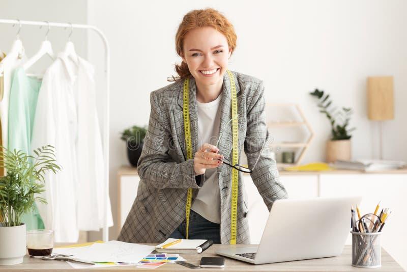 Happy designer woman work on computer in tailor workshop stock photos