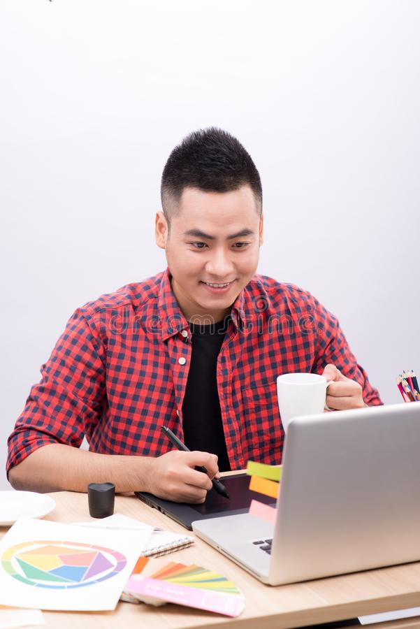 Happy designer working on his laptop in creative office royalty free stock image