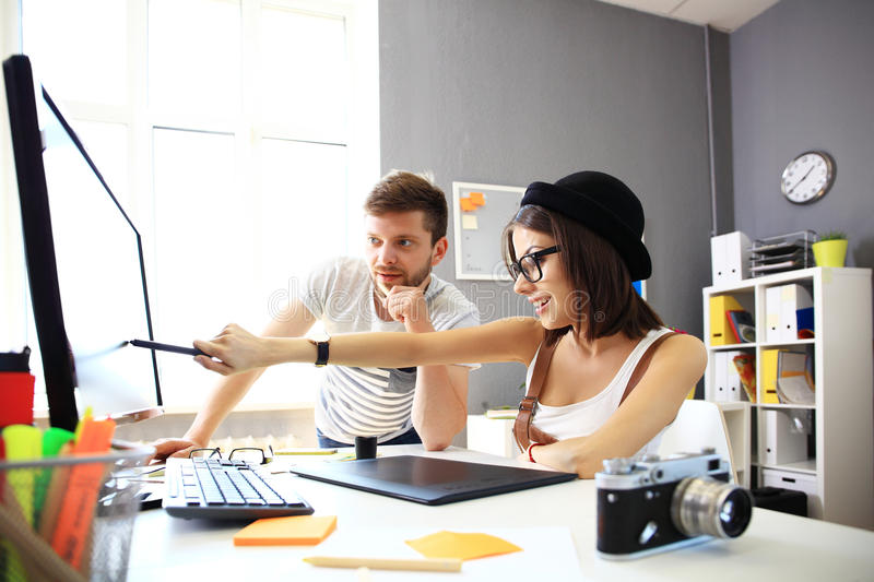 Happy designers working on a document with colleagues working stock image