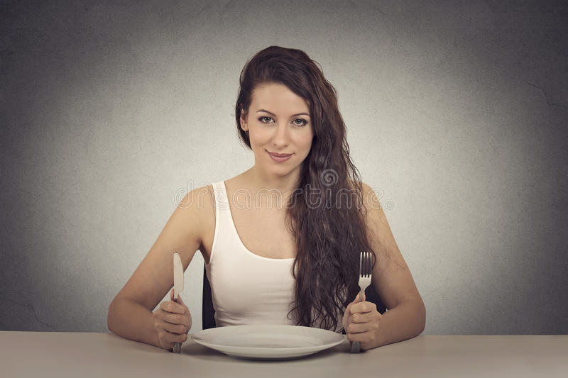 Happy dieting woman. With knife and fork stock photos