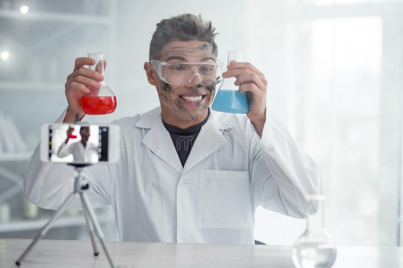 Happy dirty blogger after the experiment. I am pleased. Nice cheerful dirty fair-haired young blogger and wearing uniform and holding test tubes while making new stock images