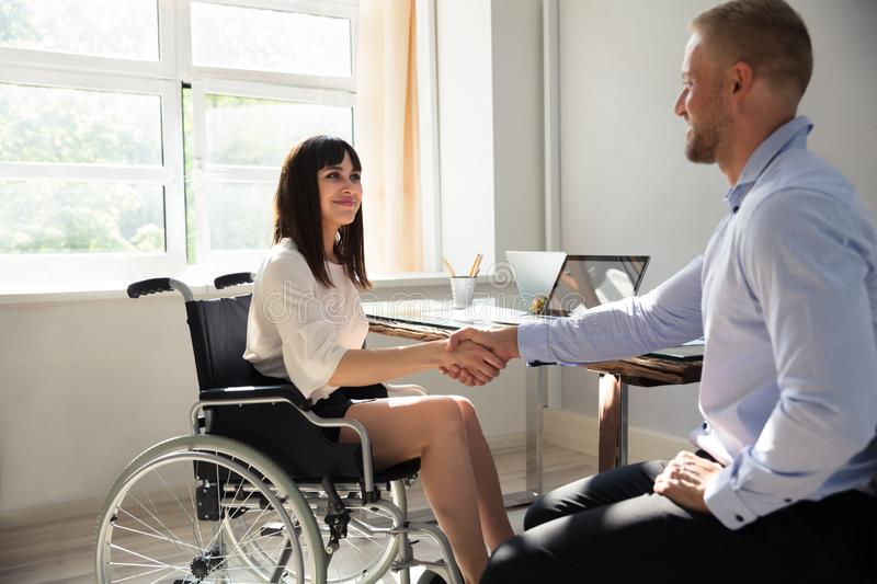 Disabled Businesswoman Shaking Hand With Her Partner royalty free stock photo