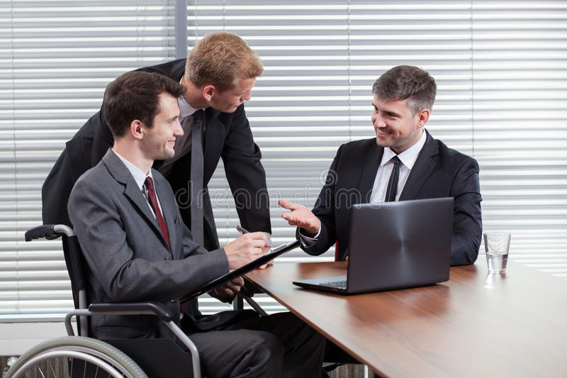 Happy disabled man during business meeting stock photo