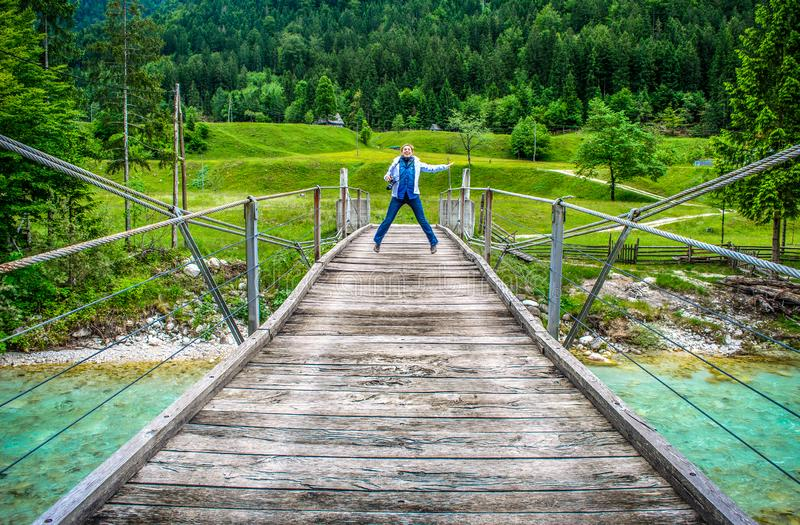 Happy distant woman jump of a wooden pedestrian bridge footbridge over river Soca in Slovenia in wild nature background.  royalty free stock photography