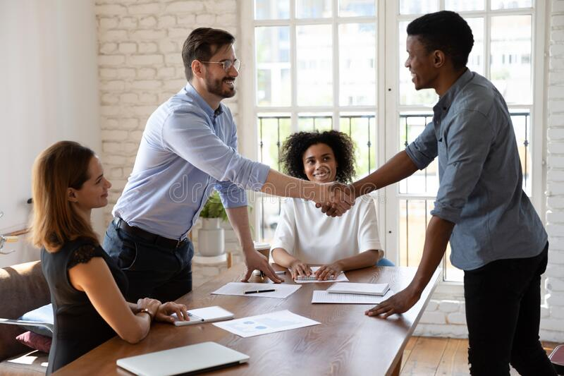 Happy diverse business partners shaking hands, making agreement royalty free stock images