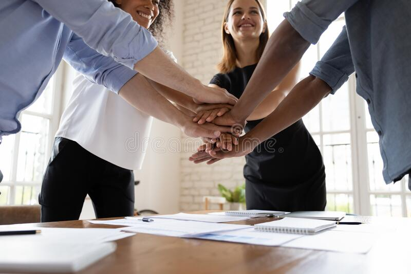 Happy diverse business people stacking hands, celebrating success royalty free stock photography