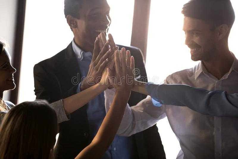 Happy diverse business team give high five motivated by success royalty free stock photography