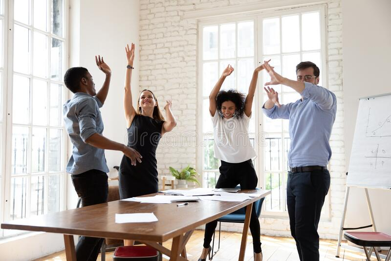 Happy business people celebrating success, dancing at meeting in boardroom stock photography