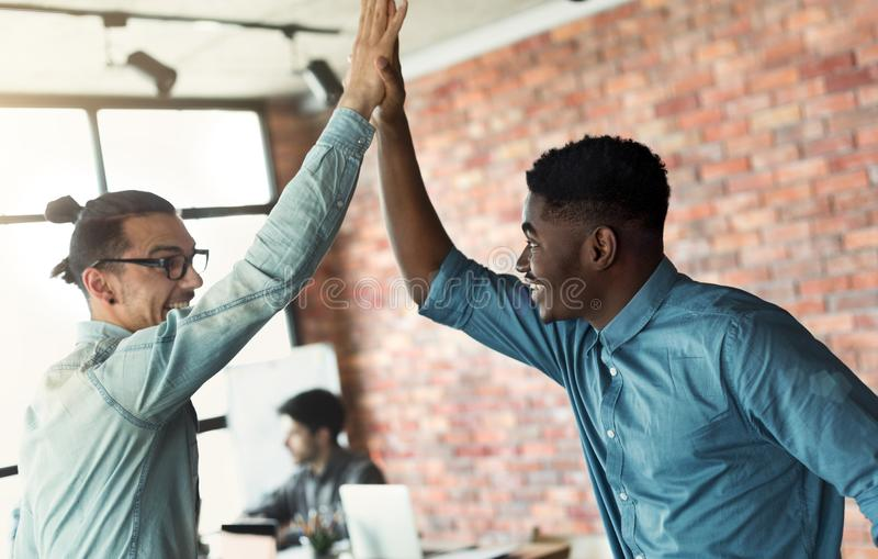 Happy diverse colleagues giving high five, enjoying partnership royalty free stock image