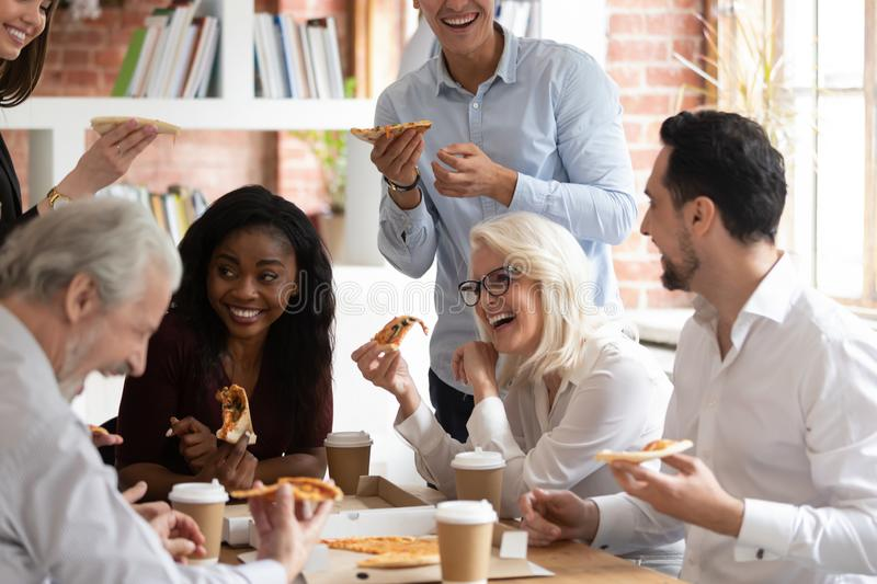 Happy diverse colleagues have lunch eating pizza together. Overjoyed multiracial employee have fun eating pizza drinking coffee in office together, smiling happy royalty free stock photo