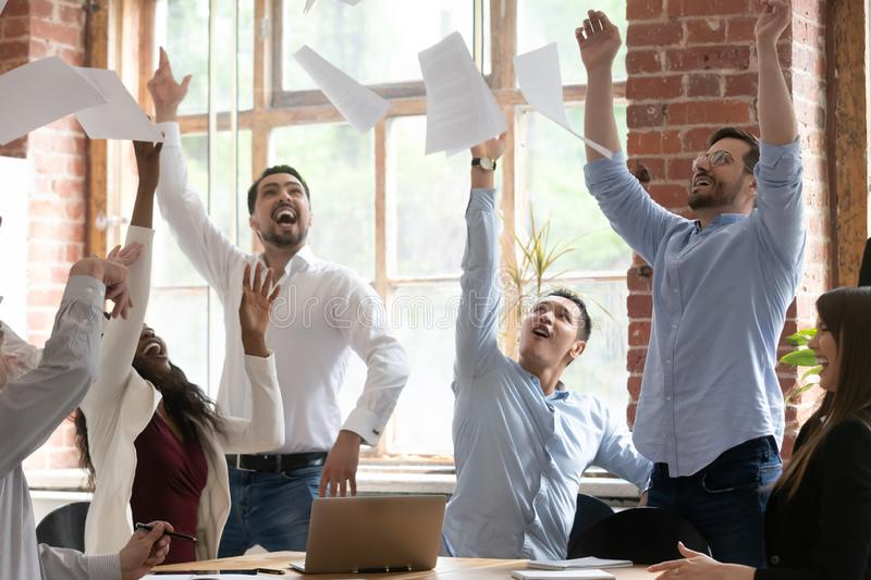 Happy diverse colleagues throw papers celebrating success. Excited diverse employees throw up in air paper documents celebrate successful business project launch stock photo