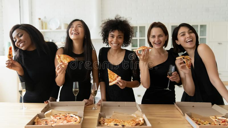 Happy diverse elegant women drink champagne eat pizza in kitchen stock images