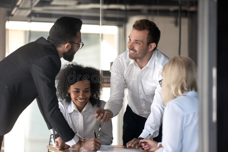 Happy diverse employees brainstorming, discussing project at meeting royalty free stock photography