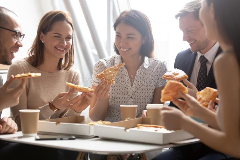 Happy diverse employees enjoying pizza, having fun during break together stock photos
