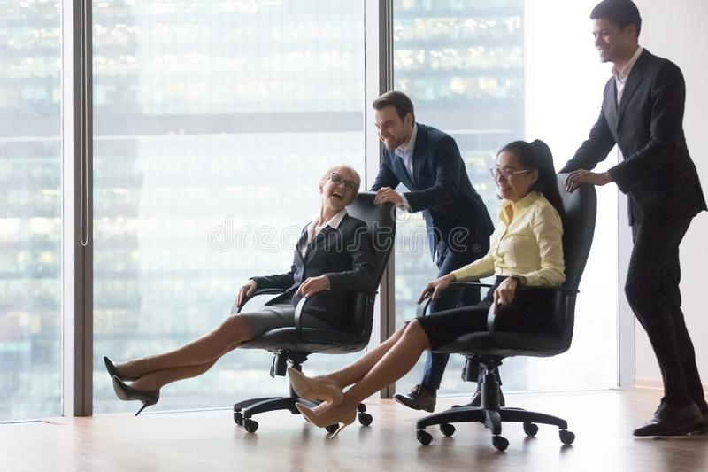 Happy diverse employees having fun riding on chairs in office royalty free stock images