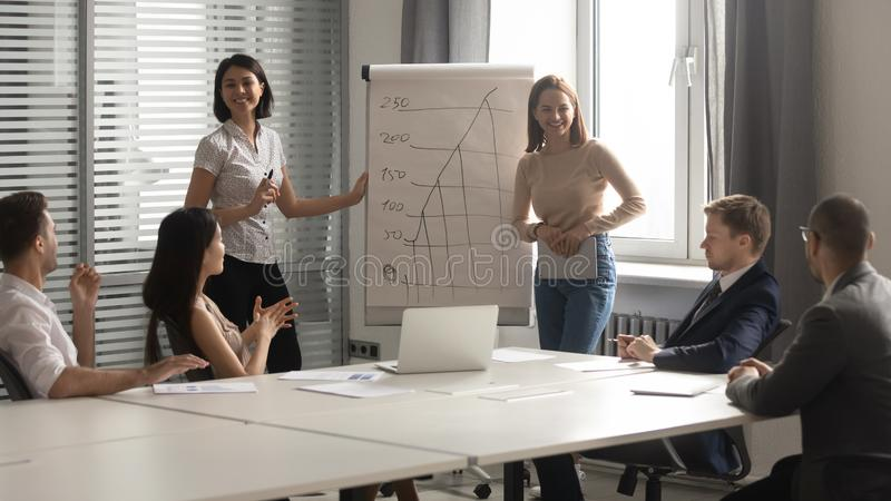 Happy diverse coaches laugh give flip chart presentation at training stock photography