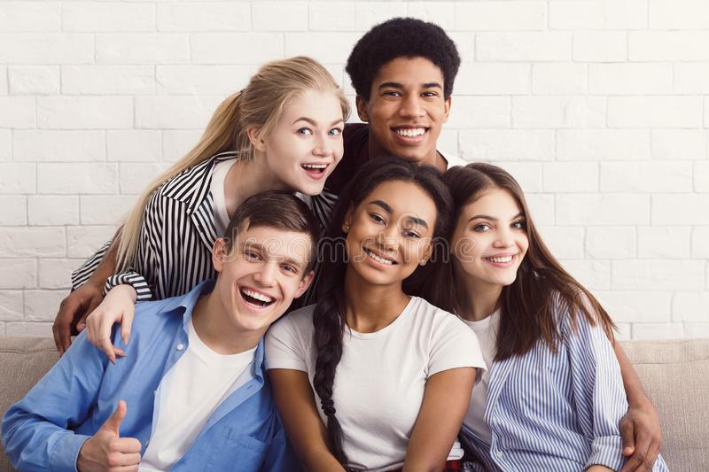 Happy diverse friends relaxing on comfortable couch in apartment stock photo